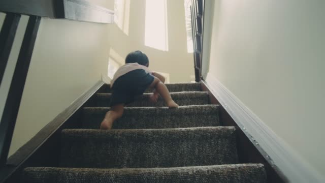 Little baby boy climbing up the steps Asian baby toddler 'first steps' walking up and down stairs at home. staircases stock videos & royalty-free footage