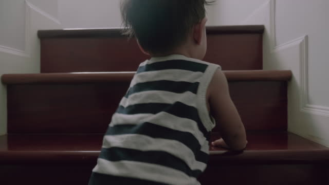 little baby (12 months) boy climbing up the steps - soltanto neonati video stock e b–roll