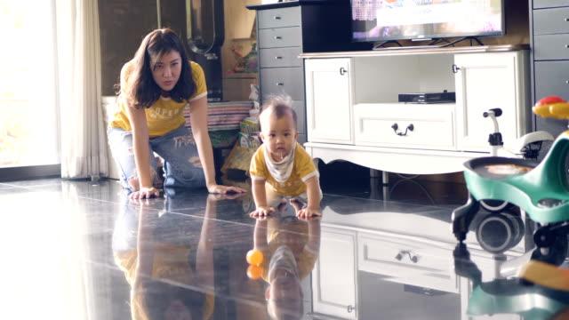 vidéos et rushes de petit garçon bébé ramper sur le sol avec la jeune mère - ramper