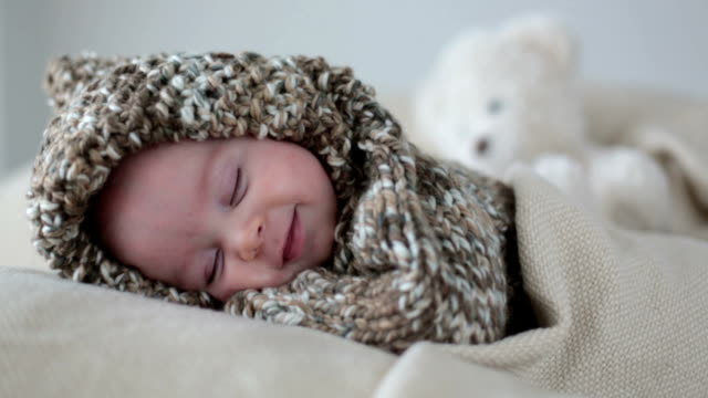Little baby boy, dressed in cute knitted teddy bear overall, sleeping and smiling in his sleep video