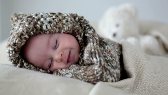 vidéos et rushes de petit garçon, vêtus de mignon nounours tricoté ensemble, dormir et souriant dans son sommeil - douceur