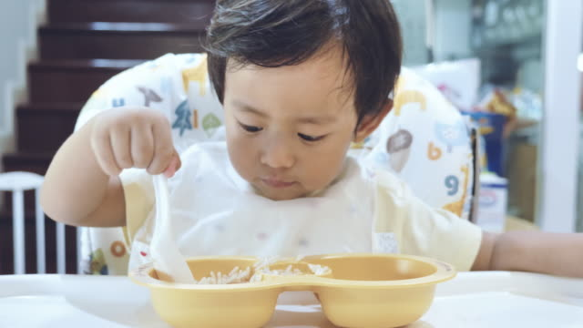 little baby boy eating baby food on high chair. - soltanto neonati video stock e b–roll