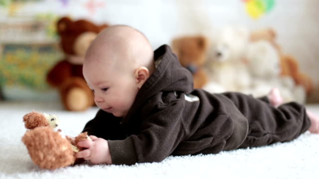 Little baby boy playing at home with soft teddy bear toys, lying down video
