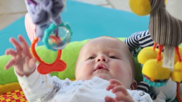 stockvideo's en b-roll-footage met kleine baby jongen spelen op speelmat - baby toy