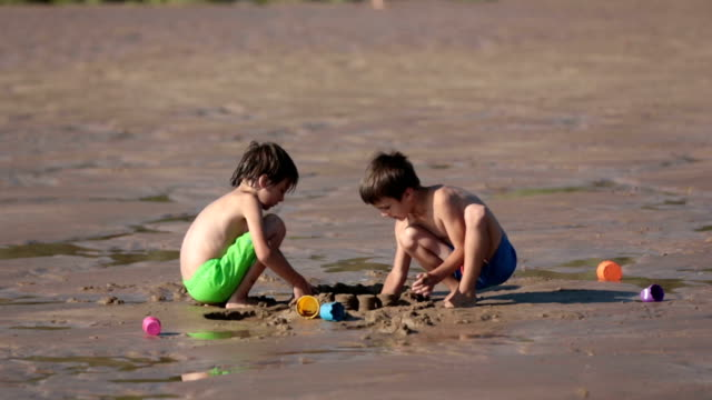 little baby boy, playing on the ocean beach with toys on sunset - solo neonati maschi video stock e b–roll