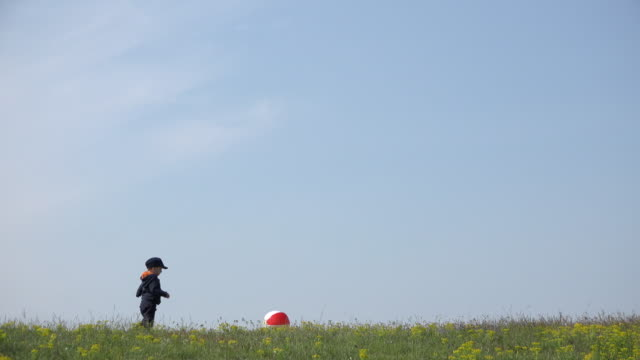 Little baby  boy playing with big ball on hill ridge, serene sky above 4K