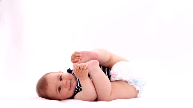 Little baby boy playing with his feet against white background video