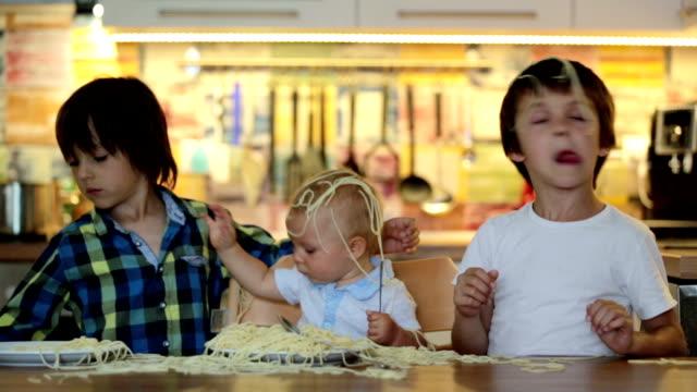 stockvideo's en b-roll-footage met kleine babyjongen, peuter, kind en zijn oudere broers, spaghetti eten voor de lunch en het maken van een puinhoop thuis in de keuken - chaos