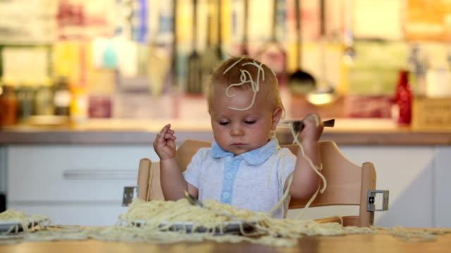 stockvideo's en b-roll-footage met kleine babyjongen, peuter kind, spaghetti eten voor de lunch en het maken van een puinhoop thuis in de keuken - background baby