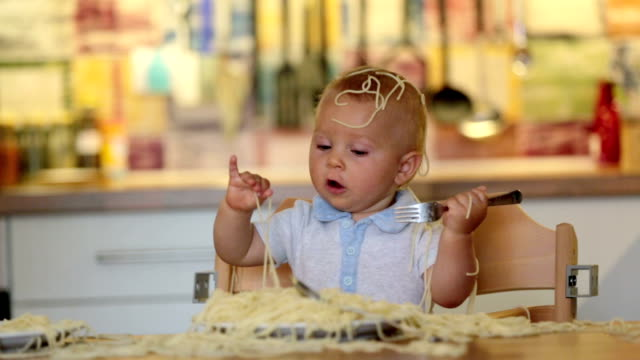 little baby boy, toddler child, eating spaghetti for lunch and making a mess at home in kitchen - birichinata video stock e b–roll