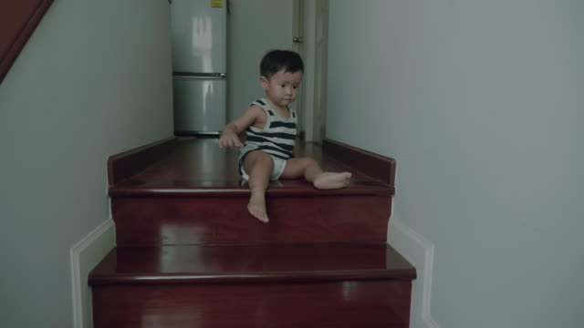 Little baby boy walking down stairs at home. video