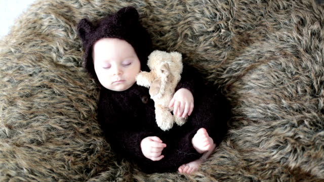 Little baby boy with knitted brown jumpsuit as a bear, sleeping at home on a furry blanket, smiling with happiness