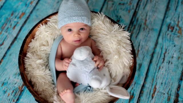 stockvideo's en b-roll-footage met baby jongetje met gebreide muts in een mand, gelukkig lachen en kijken naar camera, geïsoleerde studio opname - background baby