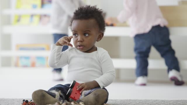 vídeos de stock, filmes e b-roll de pequeno bebê pelo jardim-de-infância - criança pequena