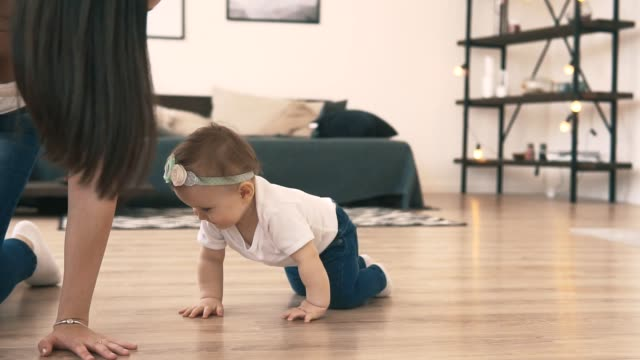 Little baby girl crawling on the floor in the room with young mother Little baby girl crawling on the floor in the room with young mother. Happy family concept in white t-shirts and jeans crawling stock videos & royalty-free footage