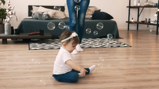 stockvideo's en b-roll-footage met babymeisje kruipen op de vloer in de kamer met de jonge moeder - wit t shirt