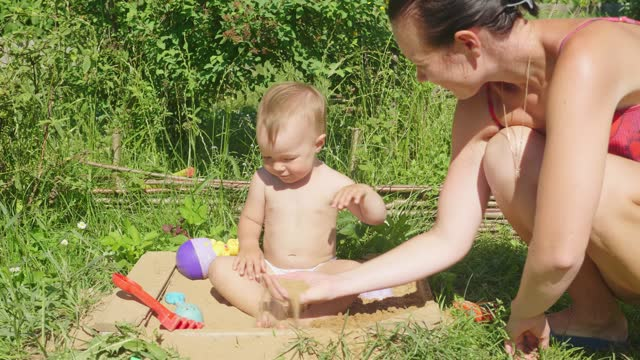 Little baby girl playing in sandbox with colorful toys