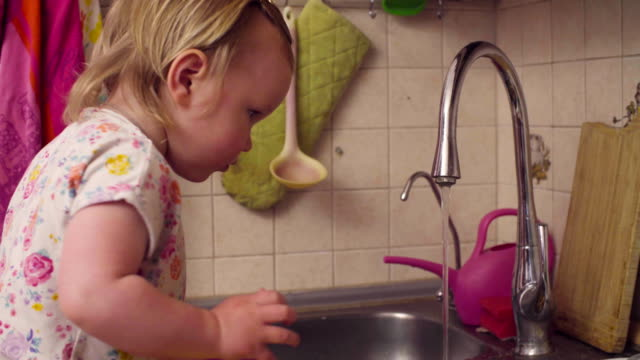 Little baby girl playing near kitchen sink video