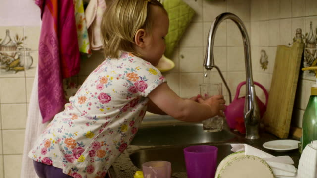Little baby girl playing washing dishes video