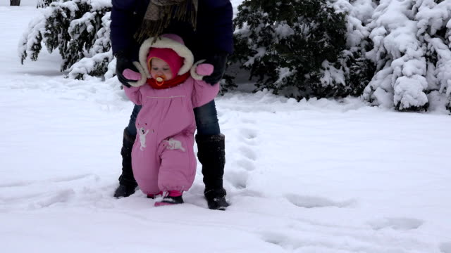 Little baby learning to walk. Woman with her toddler girl at winter park. FullHD video
