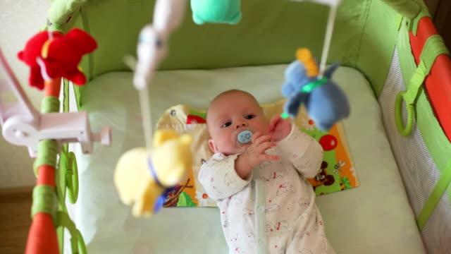 vídeos de stock, filmes e b-roll de bebê pequeno que encontra-se em uma ucha e que olha o móbil - mobile