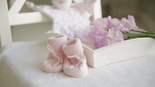 Little baby pink booties for a newborn on the background flowers and toys Little baby pink booties for a newborn on the background flowers and toys baby booties stock videos & royalty-free footage