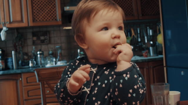 little baby sitting on the table and eating biscuit - giovane nell'animo video stock e b–roll