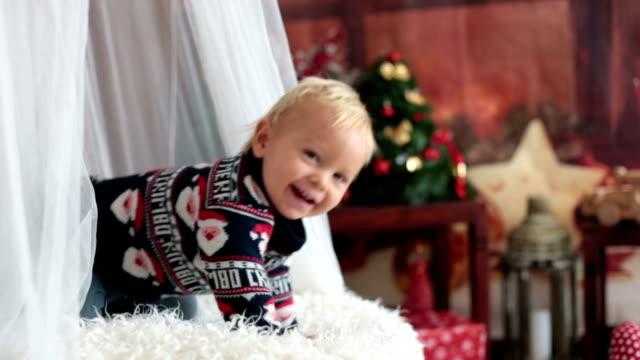 lilla baby småbarn pojke, leker med juldekoration i hemmet, studio skott, jul bakgrund - christmas gift family bildbanksvideor och videomaterial från bakom kulisserna