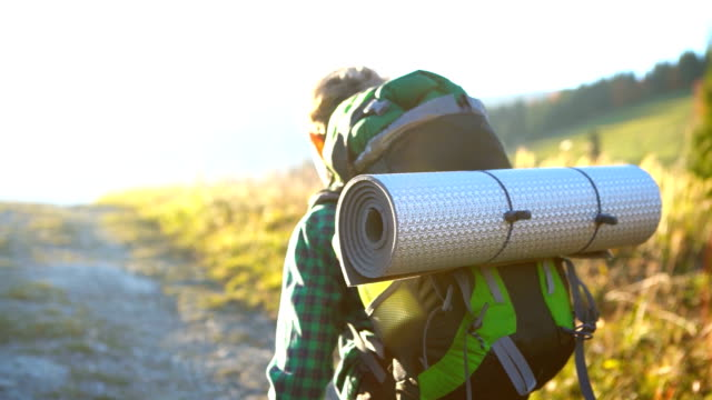 little backpacker walking by village path with rolled-up sleeping mat - campeggio video stock e b–roll