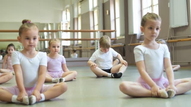 バレエクラスの前に伸びる小さなバレリーナとバレエダンサー - 男の子点の映像素材/bロール