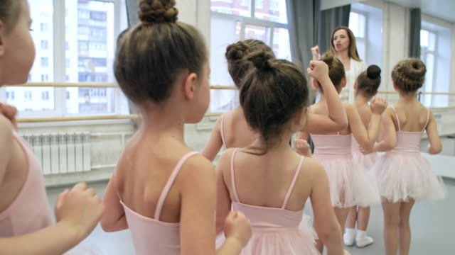 vídeos de stock e filmes b-roll de little ballerinas learning dance moves - tule têxtil