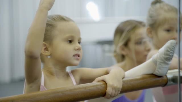 kleine balletttänzerin dehnen ihr bein auf die barre und lernt, wie man richtig schlank - gymnastikanzug stock-videos und b-roll-filmmaterial