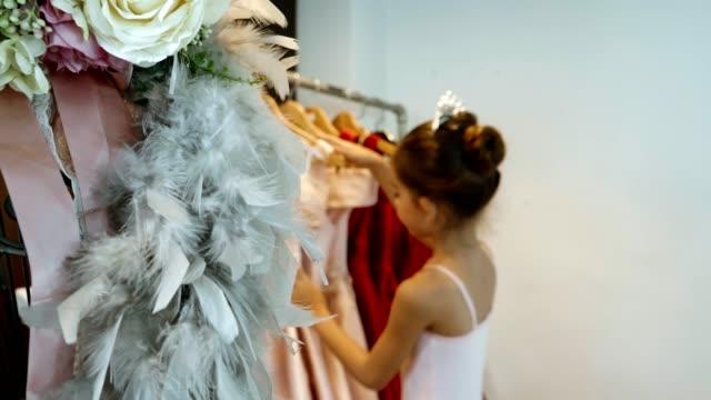 little ballet girl choosing clothes on rack - paczka sukienka filmów i materiałów b-roll