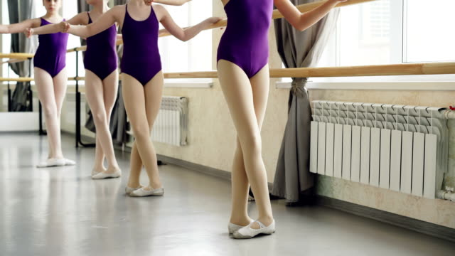 little ballet-dancers are practising battement tendu during lesson in ballet school. bright bodysuits, white pointe-shoes, ballet barre and light dancing hall are visible. - body abbigliamento sportivo video stock e b–roll