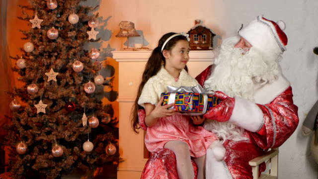 Little beautiful girl getting present from Santa Claus. Looking happy video