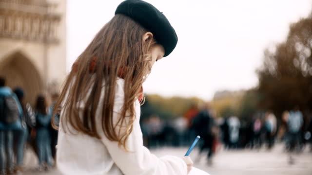 vídeos de stock, filmes e b-roll de menina bonita com o notebook sentado perto de notre-dame de paris e o esboço de desenho - moda parisiense