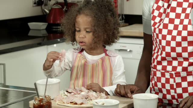 HD: Little Biracial Girl Eating Pizza Toppings Supervised By Carer/ Mother video