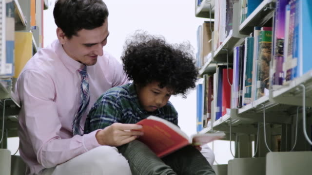 Little Black boy students and teacher reading book in library. video