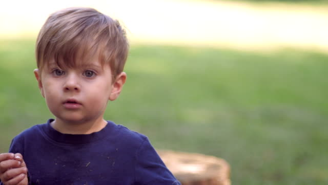 Little blond boy looking at camera waving and playing with toy in slow motion video