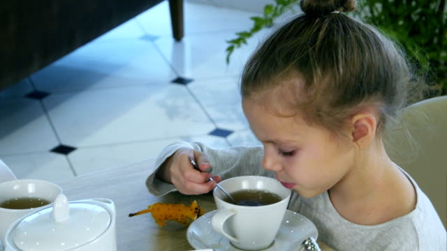 little blond girl drinking tea from spoon while her parents are busy with tablet - lingua russa video stock e b–roll