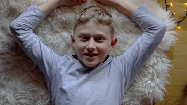 4k little blonde boy reclines on sheep-skin mat smiling - tappeto video stock e b–roll
