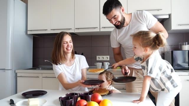 little blonde girl helping her parents to cook pancakes - naleśnik filmów i materiałów b-roll