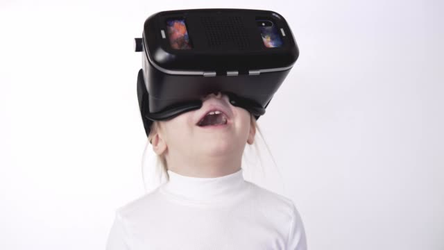 Little blonde girl in white shirt watching 360 video, wearing VR headset