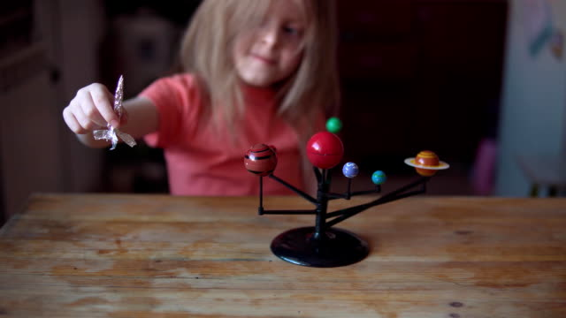 Little blonde girl plays with the layout of the solar system.