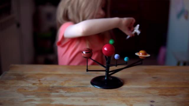 liten blond flicka leker med layouten av sol systemet. - flickbaby bildbanksvideor och videomaterial från bakom kulisserna