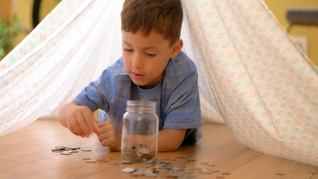 Little boy adding coins to jar. Little boy adding coins to jar full of money under play tent made from bed sheet. piggy bank stock videos & royalty-free footage