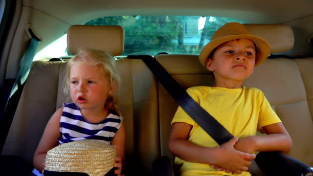 Little boy and girl are riding in the car and talking to each other - video