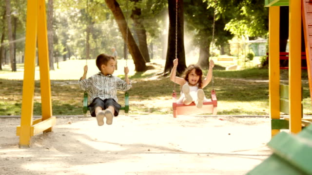 Little boy and girl are swinging on a swing. video