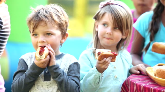 Little boy and girl eating hotdogs Two children standing with a group eating hotdogs. The little boy is 3 years old and the girl is 4. hot dog stock videos & royalty-free footage