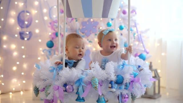 little boy and girl fun christmas tree - poroże filmów i materiałów b-roll